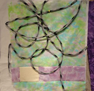 Light green and pale purple background with black and white bias loops pined to the surface.