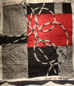Black White and burgandy fabric with black and white bias strips looping across the sruface
