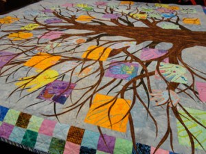 Mulit colored tree crown with childres' hands amoung the branches.