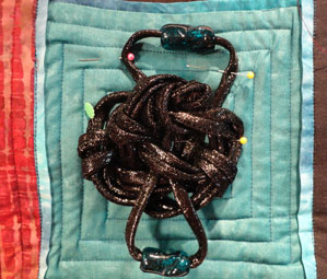 Close up of one of the knots pinned to the quilt top