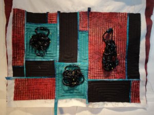 Full shot of quilt with DMC colors/fabric and black knots on top