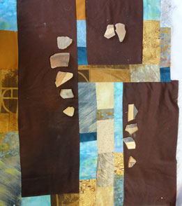 Blue and brown quilt with pot shards on top