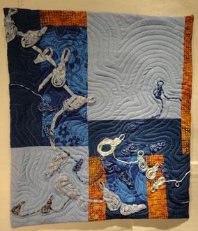 full shot of the quilt showing the frogs on a blue and deep orange background.
